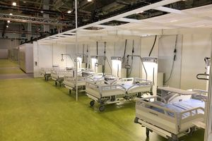 View into the Berlin trade fair hall 26: Our hospital bed Evario contributes to excellent patient care. The green floor indicates the area for mild cases, the intensive care area is blue.